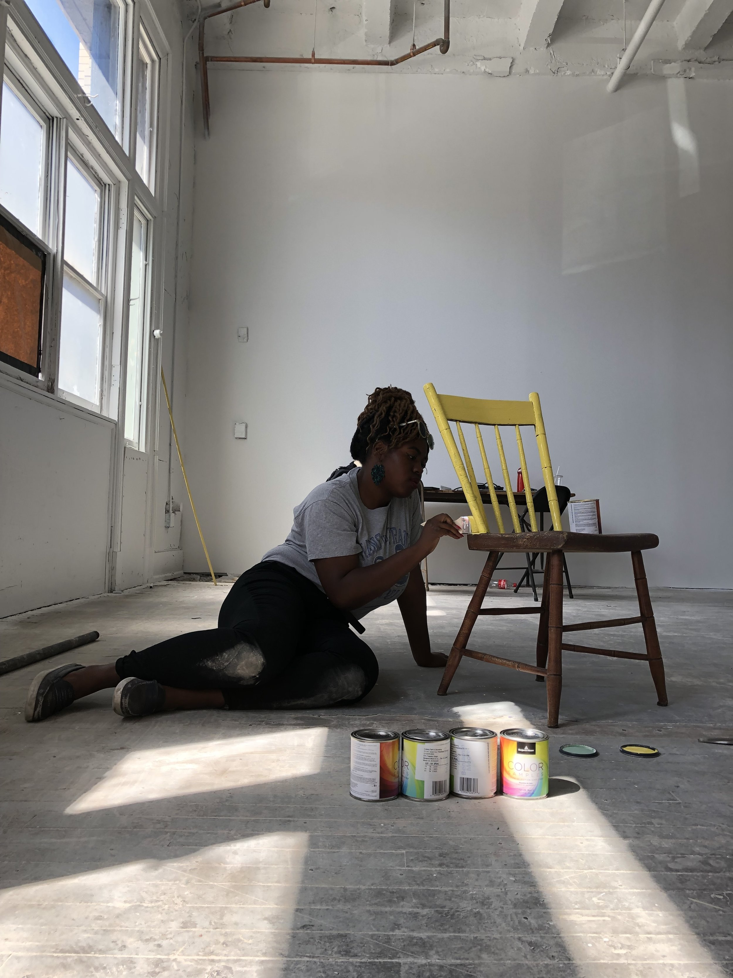We'll be using thrifted chairs that we paint with some Triple Bottom colors. Here's Sola doing a trial run!