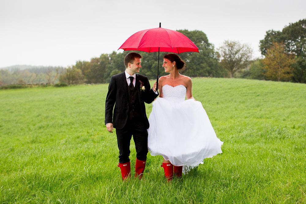 Bryllup i regnvær. Brudepar med matchende rød paraply og røde støvler.