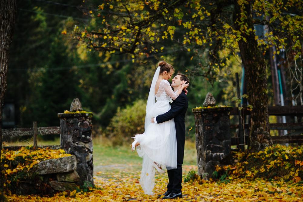 Høstbryllup. Brudgommen løfter bruden i vakkert bryllupsbilde omgitt av fantastiske høstfarger.