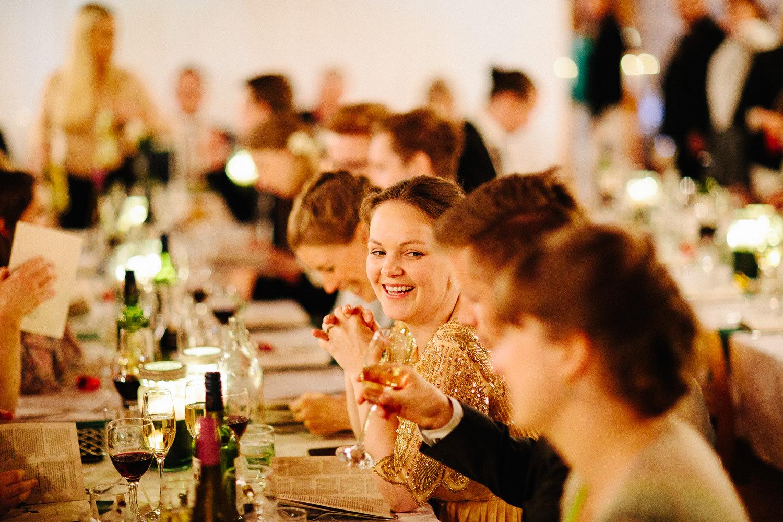 Gjester smiler og ler under bryllupsfest
