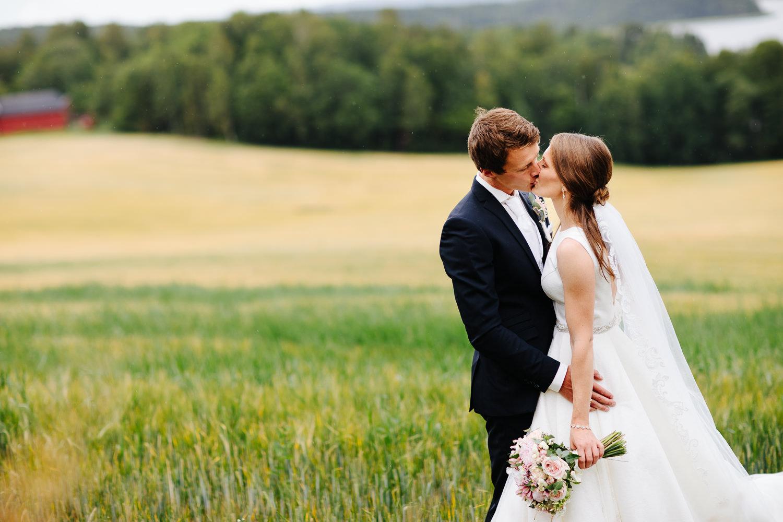 Brudepar kysser i åkeren, bryllupsbilde i Sarpsborg