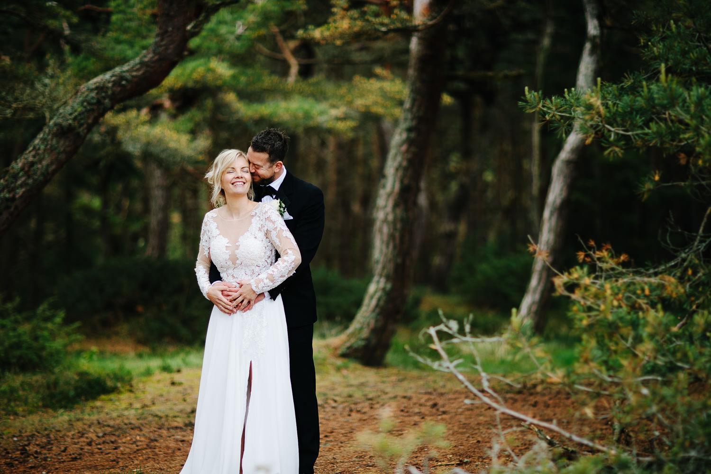 Et vakker bryllupsbilde av brudepar i skogen på Storesand på Hvaler.