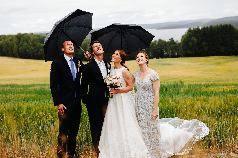 Brudepar og forlovere med paraplyer i regnvær under bryllupsfotograferingen.