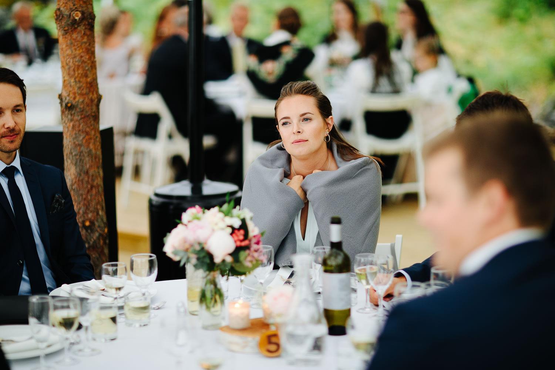 Bryllupsgjest varmer seg under et teppe fra utendørs bryllup i partytelt.