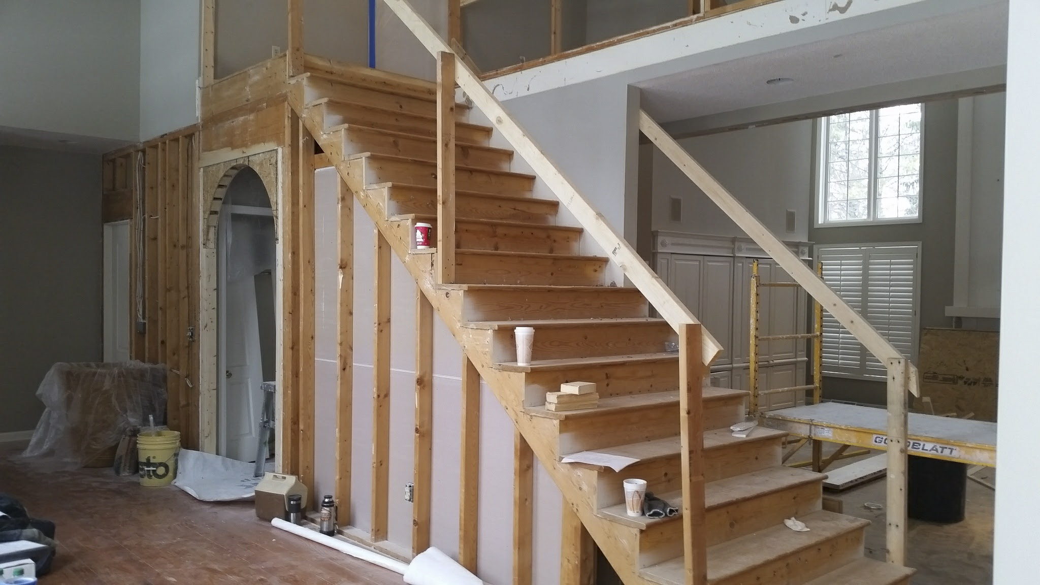 Carpeting, railings and drywall removed from stairway and foyer walls. Arched opening framed in.