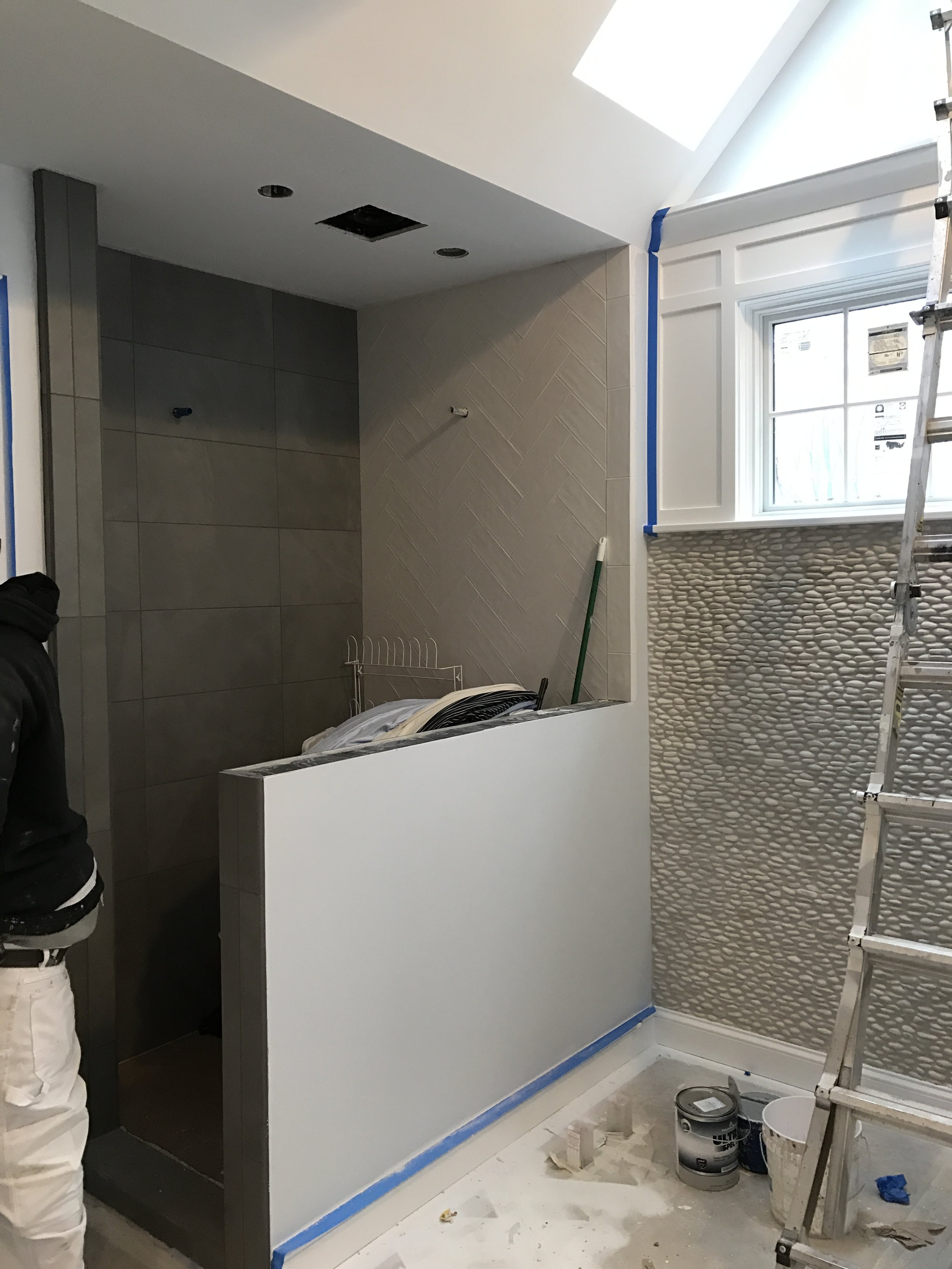 Finishing touches to tile in master bath shower