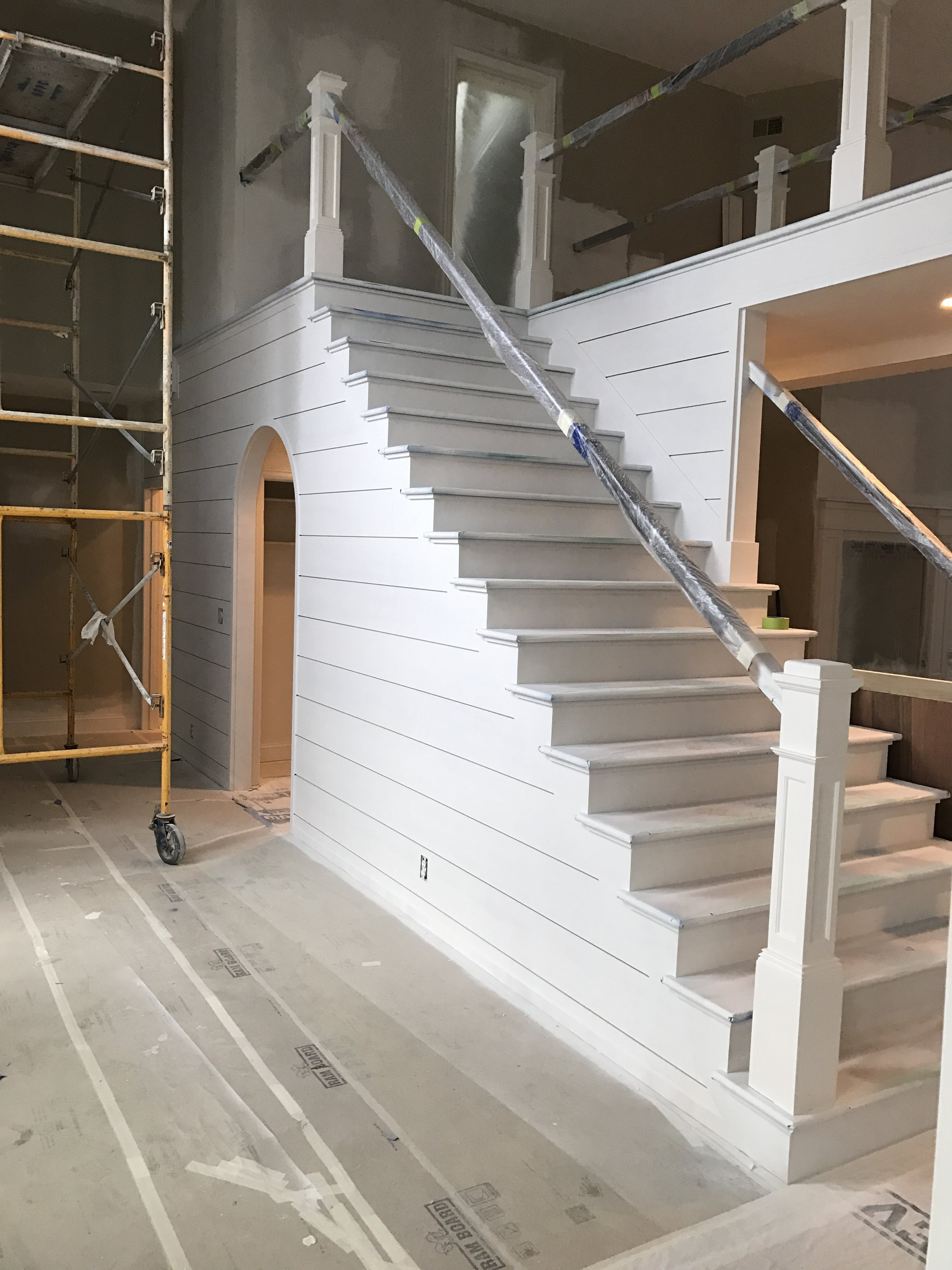 Shiplap foyer and stairwell walls with open-tread stairway primed.