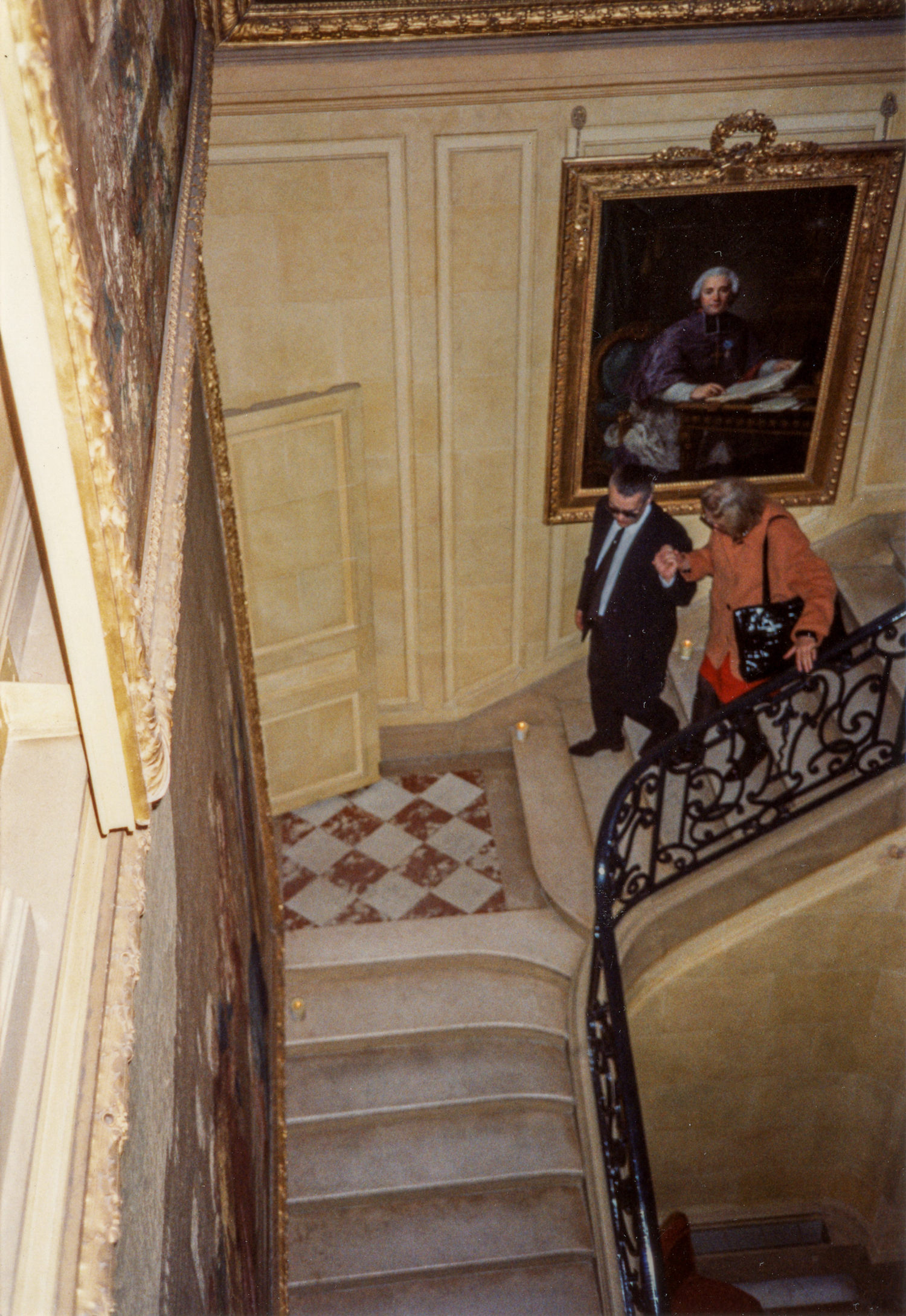 (Karl helping Carrie Donovan down the stairs of his home in Paris.)