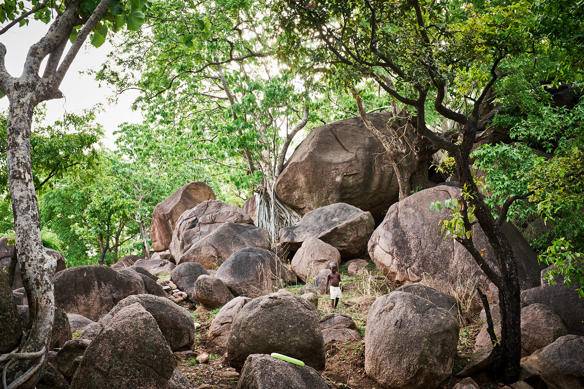 A child walks at the base of the pile of boulders where the Tiŋaana is worshipped.