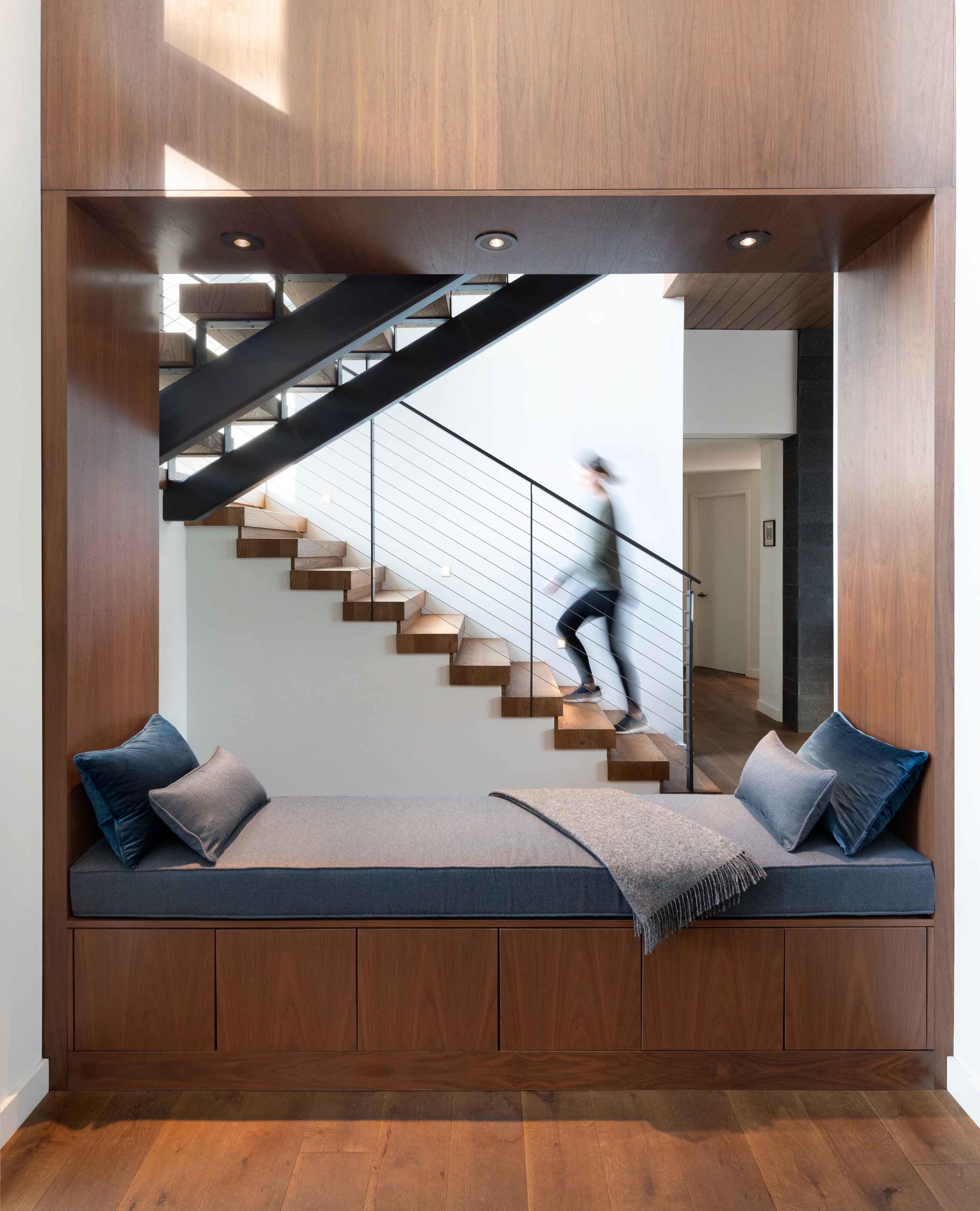 Handcrafted stair with bench seating is the heart of this purposeful home.  (Photograph by Eric Staudenmaier)