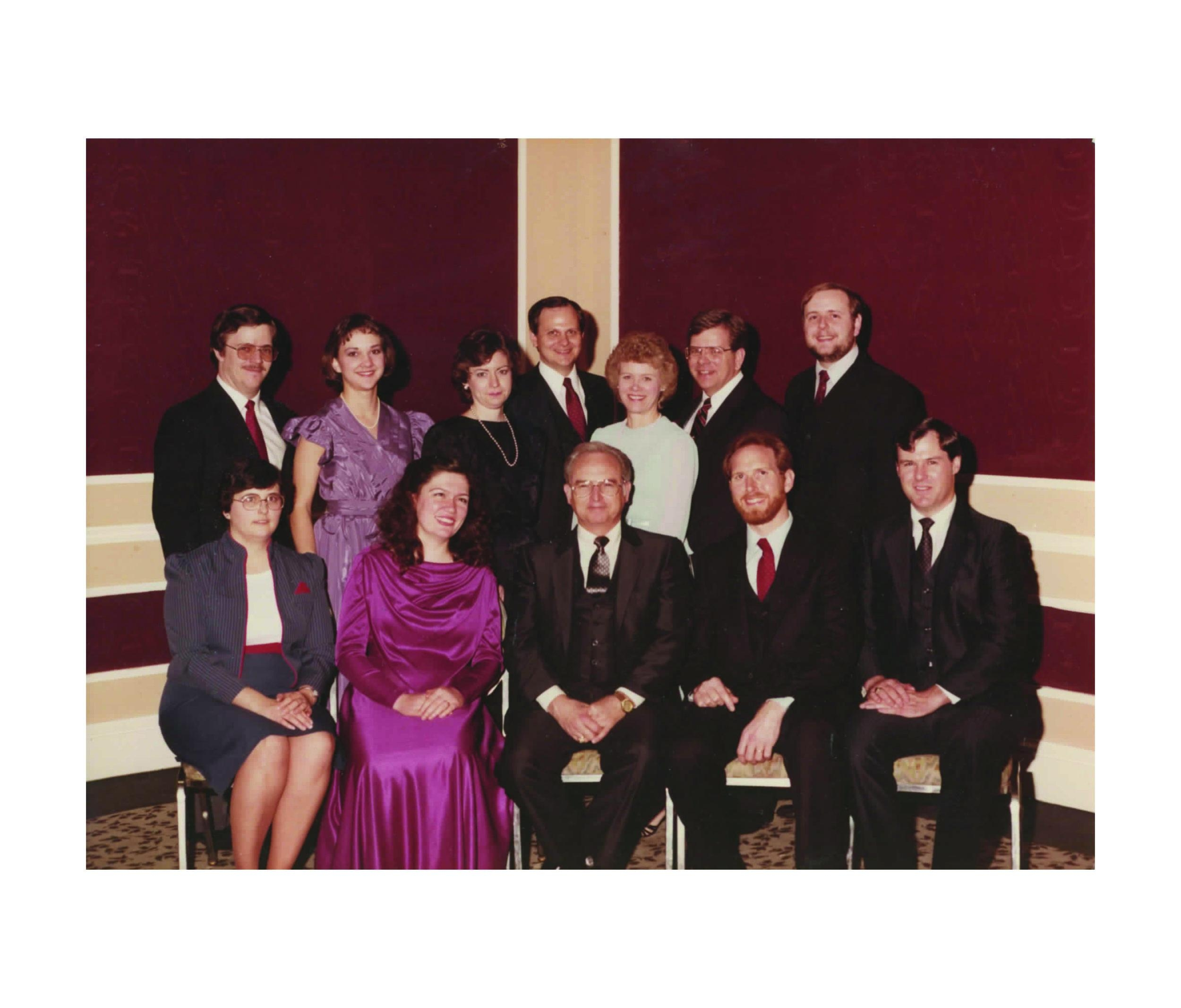 Founder Charles Simpson (sitting, center) and Beth (standing, second from the left)