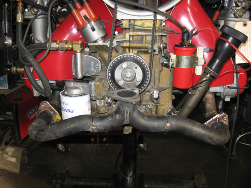 Once Derek got to hear his engine running, he decided that the exhaust may look cool, but his neighbors would care more about how it sounds (or rather how much they would notice how it sounds). So it's time to build a quieter system. We used a type 4 header and cut it into pieces. We added flanges from stock head pipes and tack welded the re-cut tubes into place.