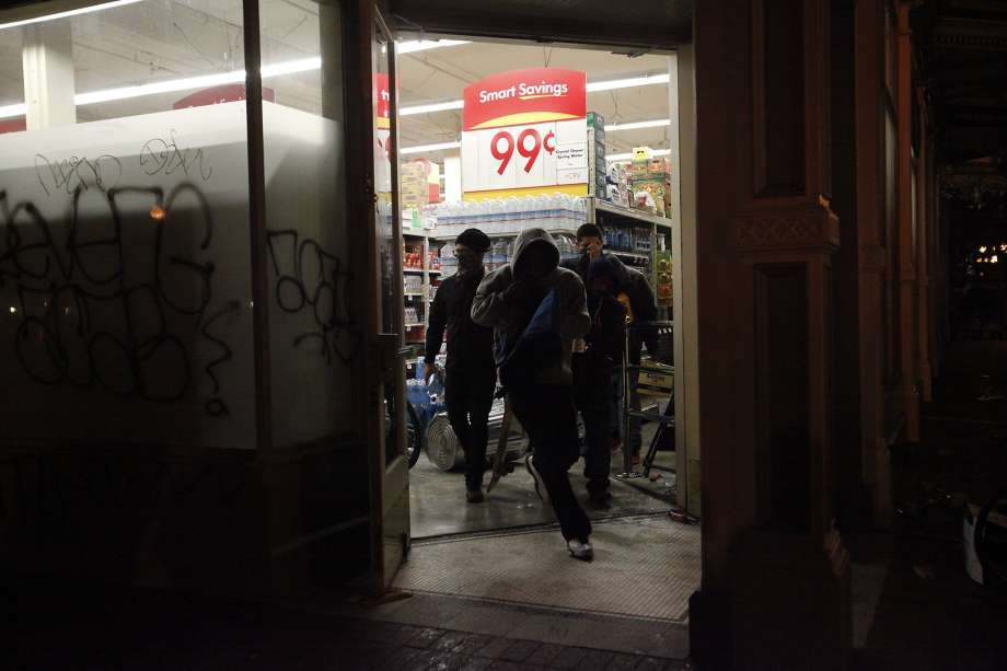 Photo: Leah Millis, The Chronicle - Vandals loot the grocery store Smart and Final after vandalizing the front and breaking the windows during a protest