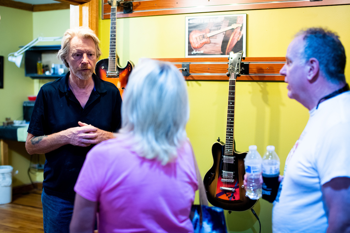 Cue Gerhards speaks with visitors at the open house at Gerhards Guitarworks