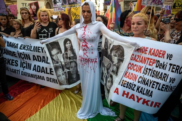 Protesters in Istanbul including an LGBT supporter painted with red tears symbolising blood, her dress.
