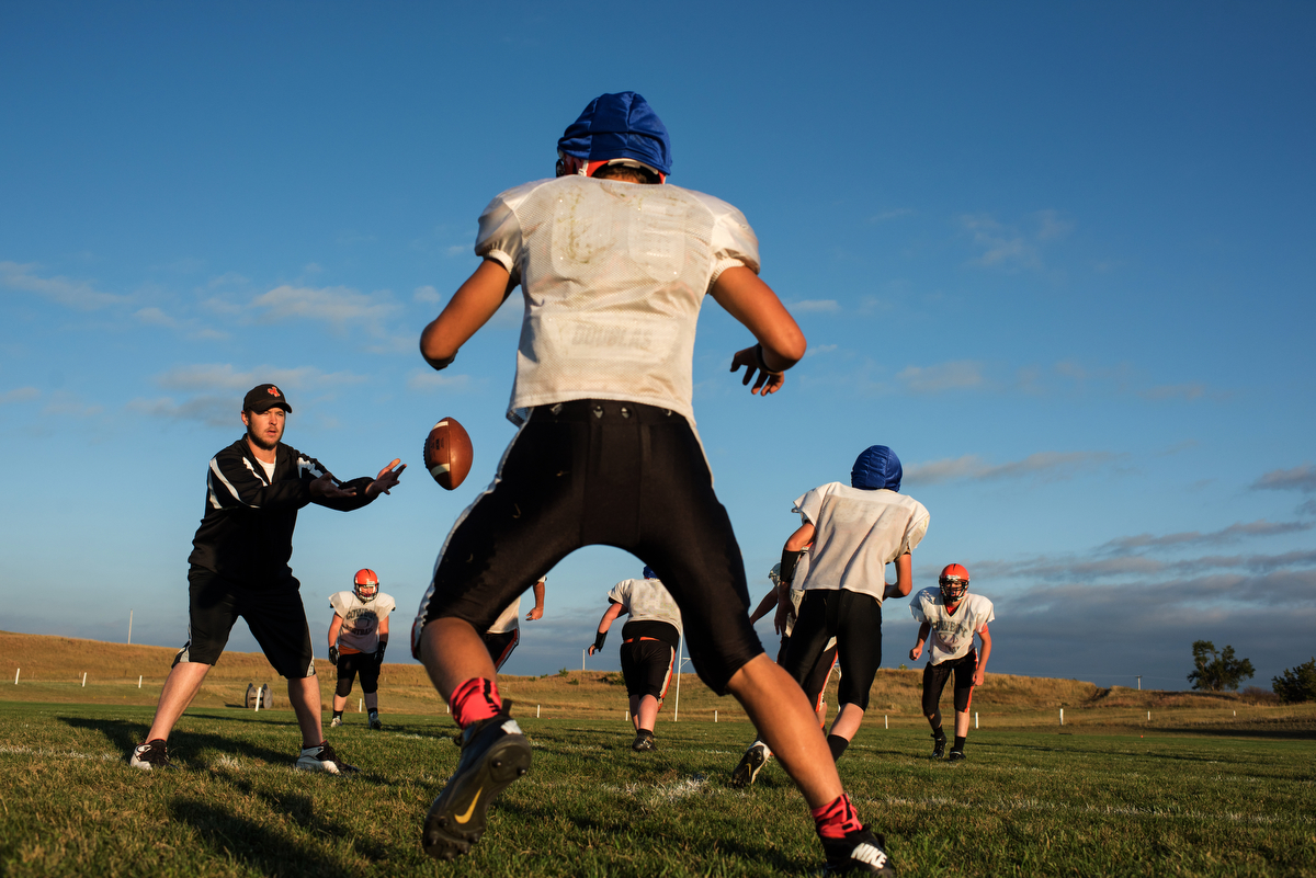 Coach Miller runs practice after school. Many of the players have to drive long distances home, and they generally work on the family ranch before school and finish their chores after practice.