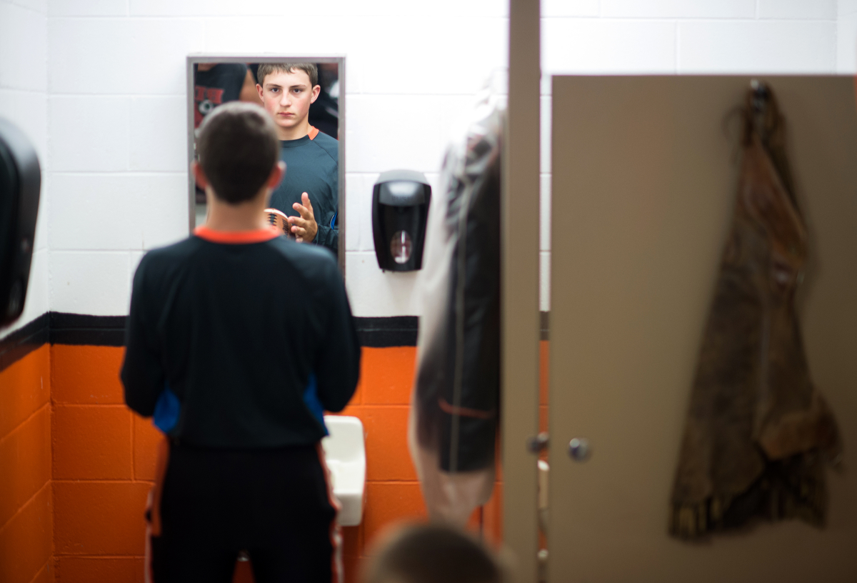 Freshman Brye Szakacs stands in front of the single mirror in the locker room before the homecoming game. Cody's locker room is only about 200 square feet, with one sink, one toilet and one shower.