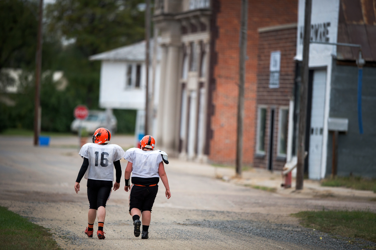 "Riley Collier and Sheldon ""Slim"" Lincoln walk the mile from the football field back to the high school through downtown Cody. The town has a custom bootmaker, a fancy vinegar store where a 4-ounce bottle can cost as much as $25, a livestock supply store, a gas station, a post office, the school, one bar, and a grocery store built and operated by high school students."