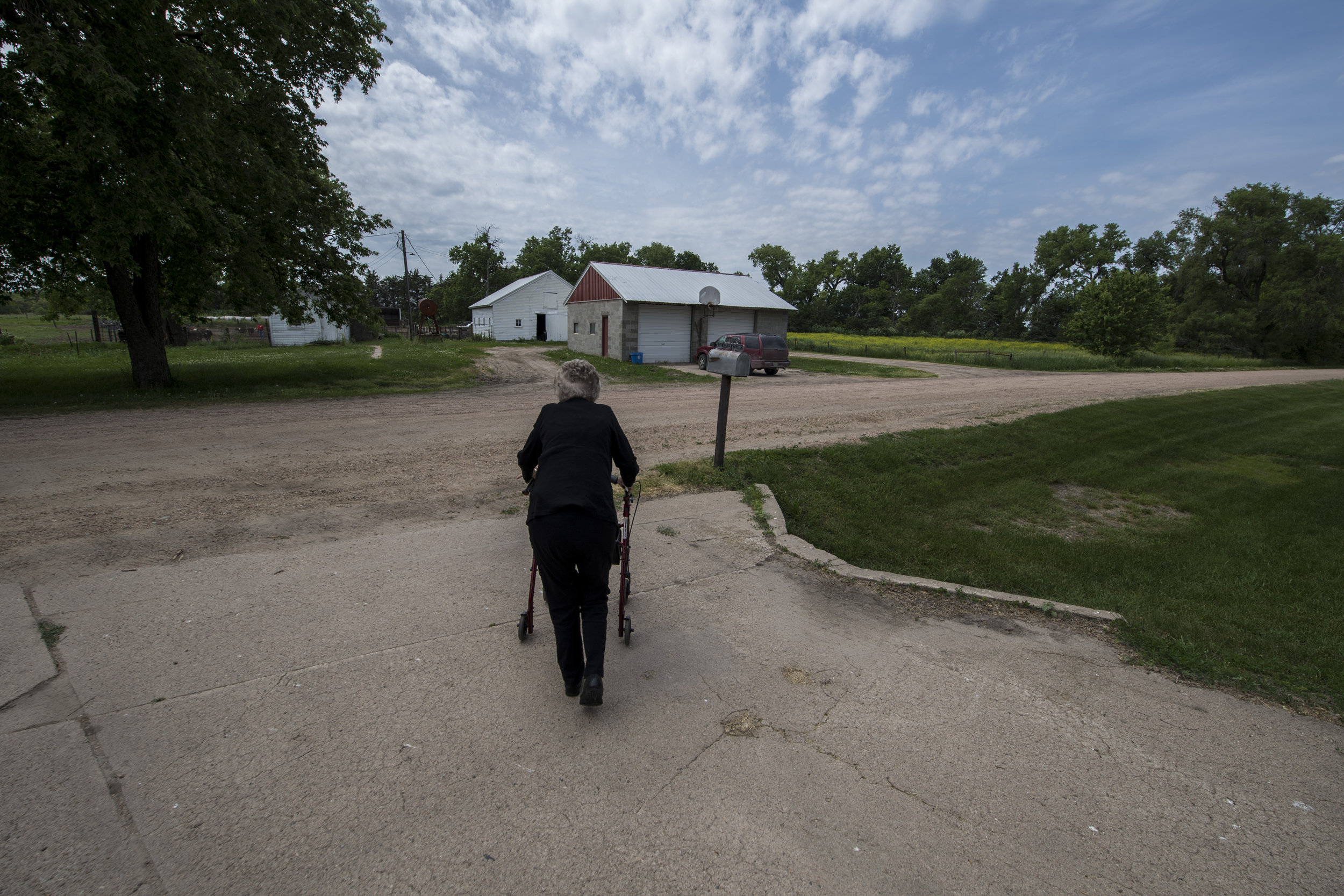 Lucille walks to the end of her driveway in Clearwater, NE. Her son John lives to her left, son Tom lives to the right.