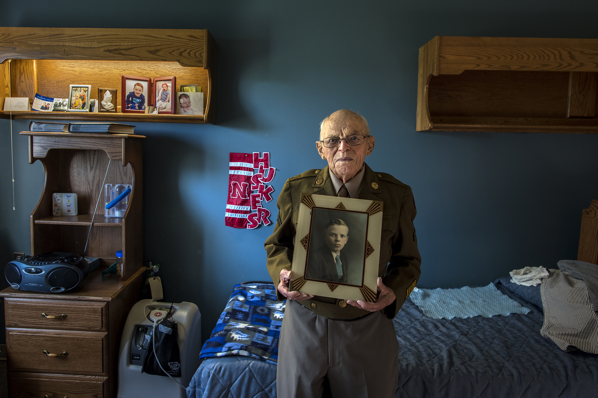 Harold Heins holding a photo of himself as a boy in his army uniform. He served in WWII and passed away in 2016 at 101 years old.