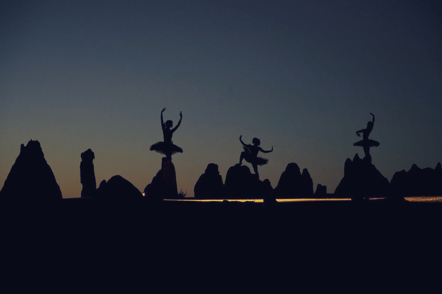 A still frame of the dancers at dusk, light from a dedo sstreamingg past them.