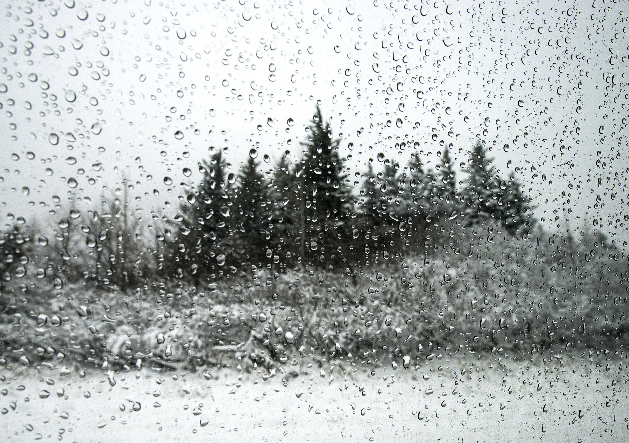 Snow-covered ground through a rain covered windshield in Alaska.