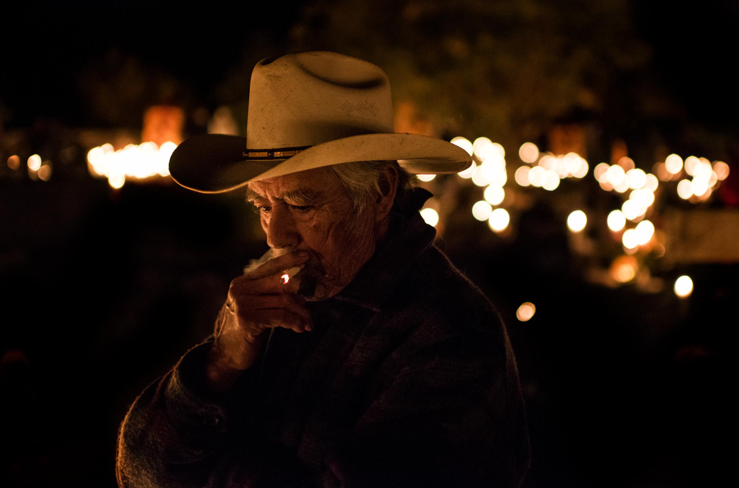 A man smokes a cigarette by his family's altar on a Lake Pátzcuaro island.