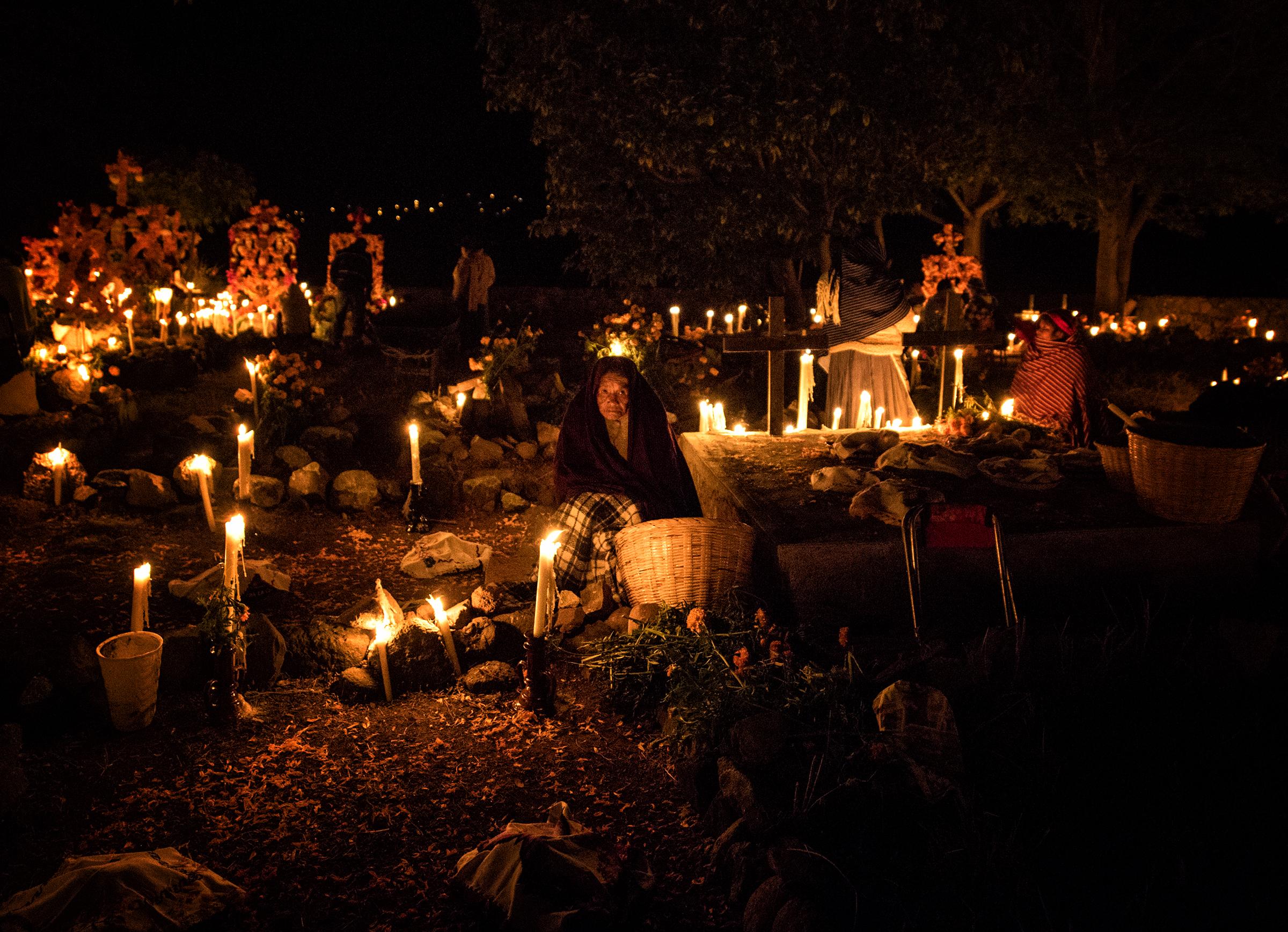 A woman among the candles on el Noche de los Muertos.