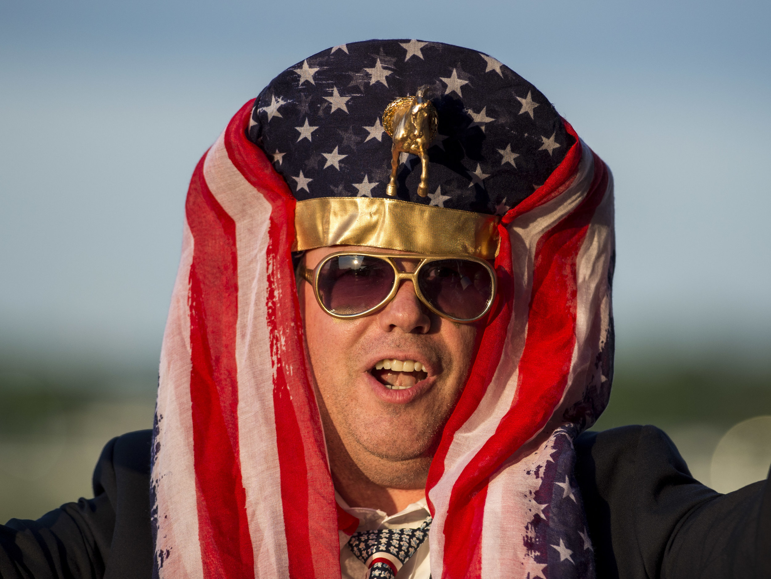 A fan of Pharoah wears a homemade Egyptian Pharaoh hat fashioned with an American flag and gold horse.
