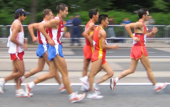 """Knee hyperextension and delayed heel rise in an interesting sport, Racewalking.   If you have been in practice long enough, you should know by now that in order to truly help an athlete you have to know their sport, the subtleties and the specifics. You have heard us talk about premature heel rise off an on for years. Today, you must consider the opposite, delayed heel rise and the bizarre loading responses that come into the kinetic chains from such a behavior.  Racewalking is a long-distance event requiring one foot to be in contact with the ground at all times. Stride length is thus reduced and so to achieve competitive speeds racewalkers must attain cadence rates comparable to those achieved by Olympic 800-meter runners for hours at a time. Most people cannot truly appreciate how fast these folks are going.  There are really only two rules that govern racewalking:  1-The first rules states that the athlete's trailing foot's toe cannot leave the ground until the heel of the leading foot has created contact.  2-The second rule specifies that the supporting leg must straighten, essentially meaning knee extension (and for some, terminal extension, ie. negative 5-10 degrees !) from the point of contact with the ground and remain straightened until the body passes directly over it. Again, essentially meaning full range knee extension for the entire stance phase of gait (early, mid and late midstance phases).   Delated heel rise ?   Clearly some folks are going to take knee extension a little more literally. Look at the fella in the red and yellow. Can you say knee HYPER extension ? This is right knee anteriormeniscofemoral impingement looming on the horizon, this is an anterior compression overload phenomenon via the quadriceps. This is often met in this sport with the  delayed heel rise  that the sport seems to often drive. Prolonging the foot ground contact phase, attempting to abide by Rule#2,""""the support leg must straighten"""", can lead to knee hyperextension if one"""