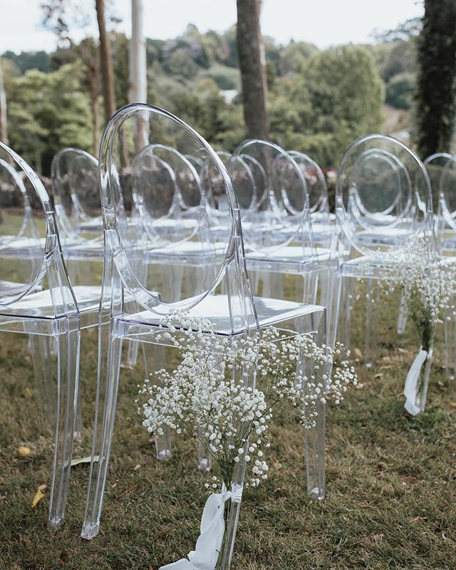 Sometimes nature around the wedding is where the eye should be drawn. We love the use of ghost chairs and simple florals to draw the eye to small details in the beauty around!  Photo by @coraleestone  Florals @rosieswildflowerco  Venue @blackwalnutvenue