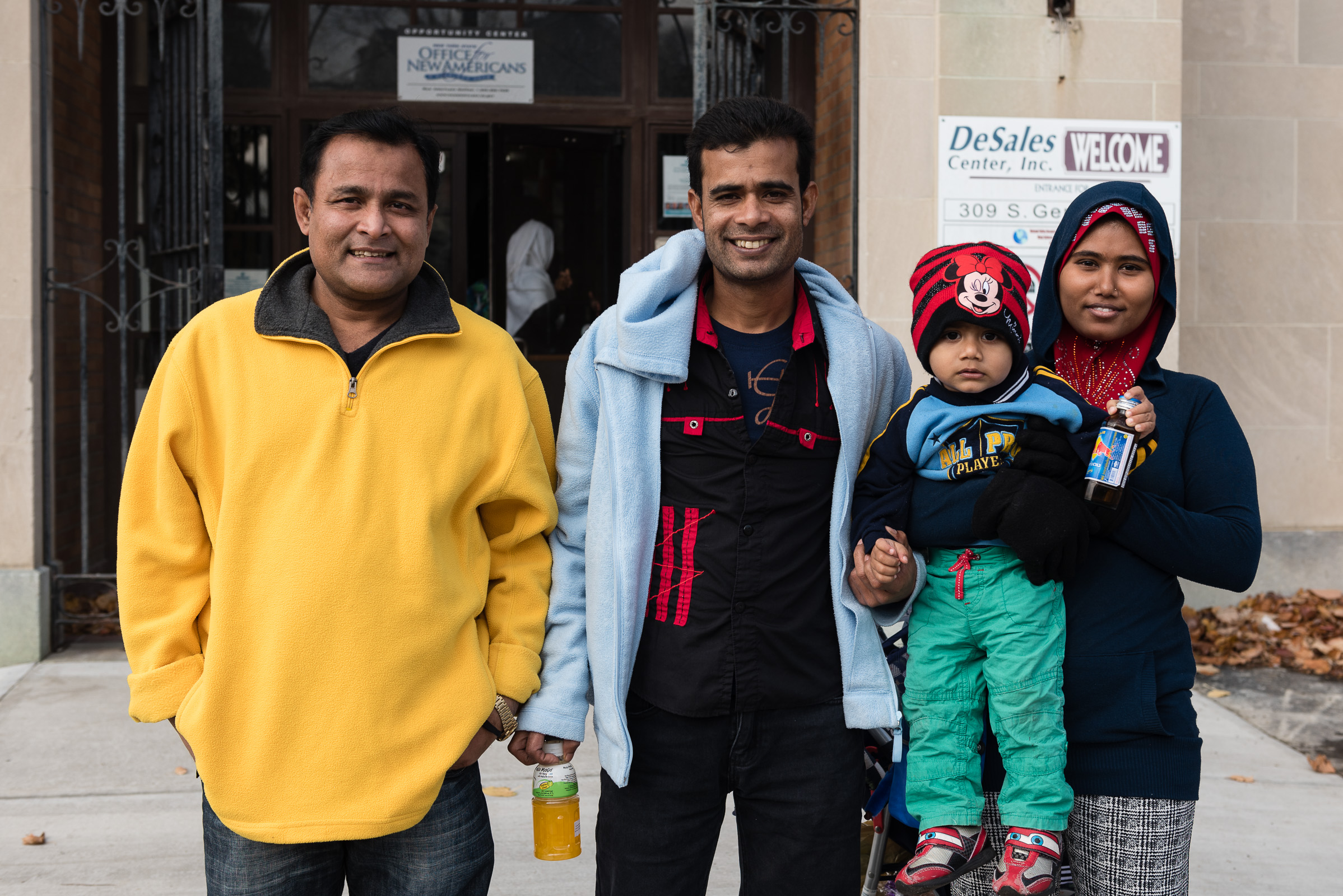 Nor Kalimullah (center) stands with his friend Abdul Alim (left) and Alim's wife and child, Jaura and Abdul (right), outside the entrance to the Mohawk Valley Resource Center for Refugees in Utica, New York. Joseph Ryder
