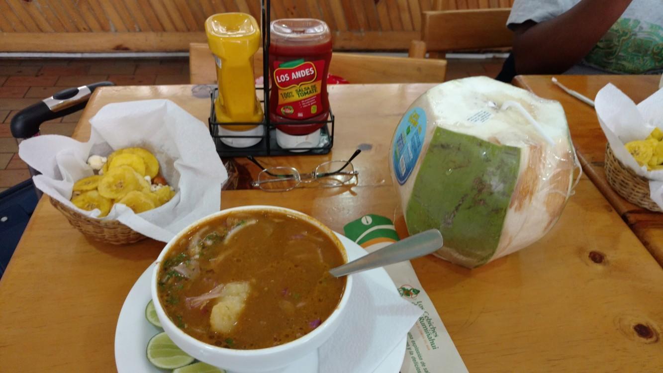 An encebollado with chifles, plus some coconut juice