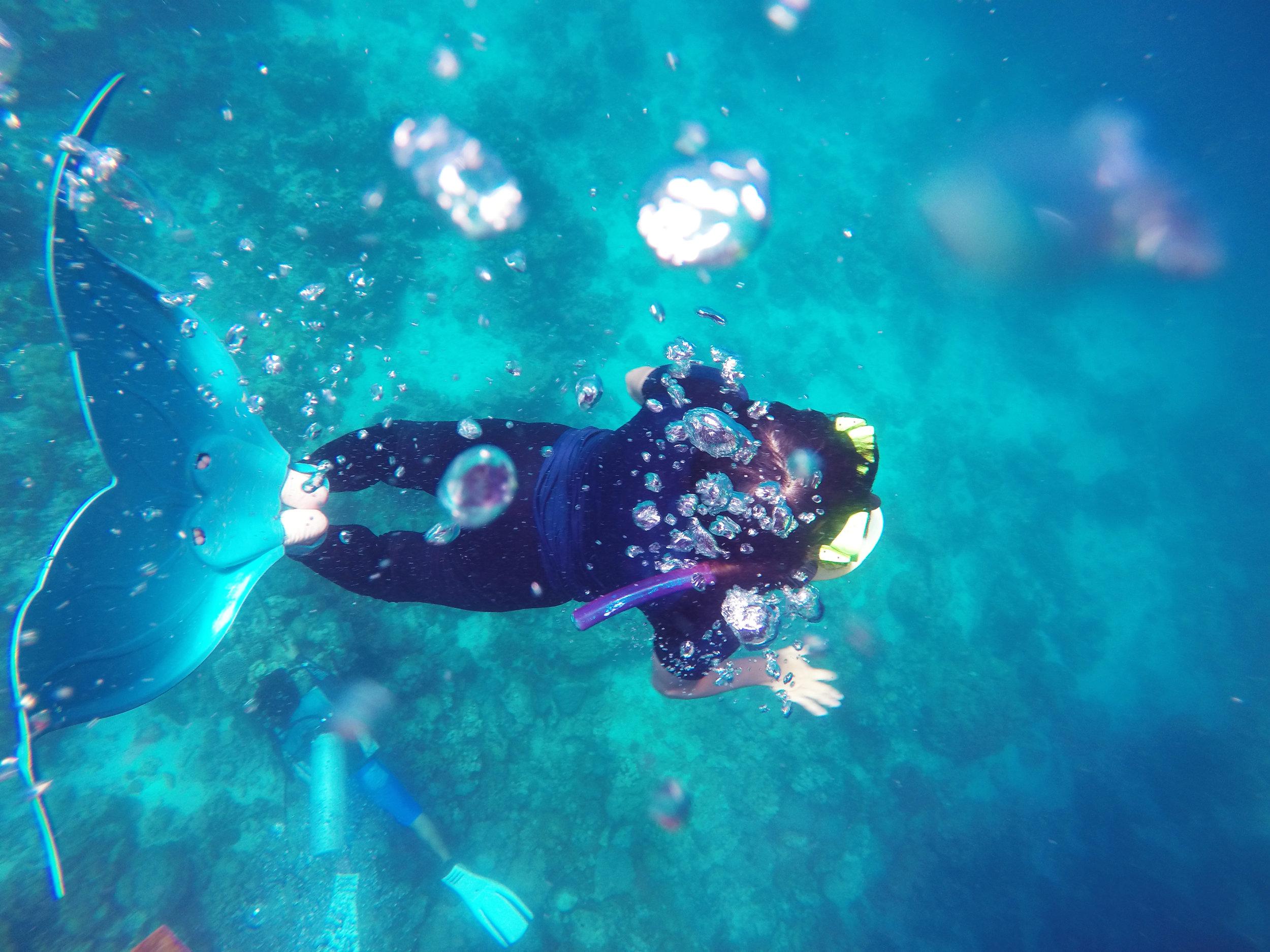 Channeling her inner mermaid, Dayanara Tan, goes for underwater cartwheels as she tries on my mermaid fins. Photo by Bianne Yee.