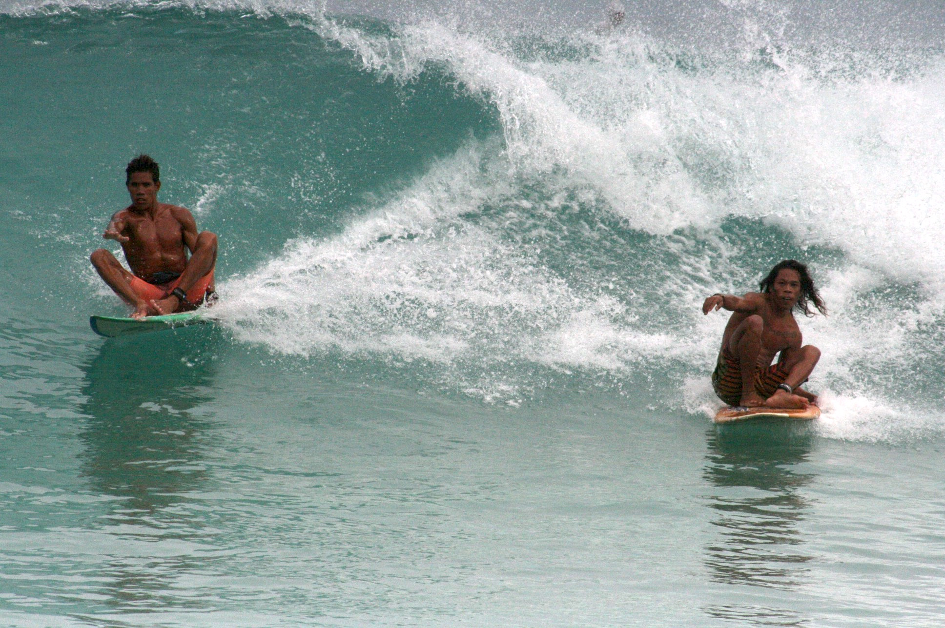 """Locals just wanna have fun. Champion skimboarder Sonnyboy """"Bayogyog"""" Aporbo (left) and Michael """"Daggy"""" Bucong share a wave seated on their surf boards."""