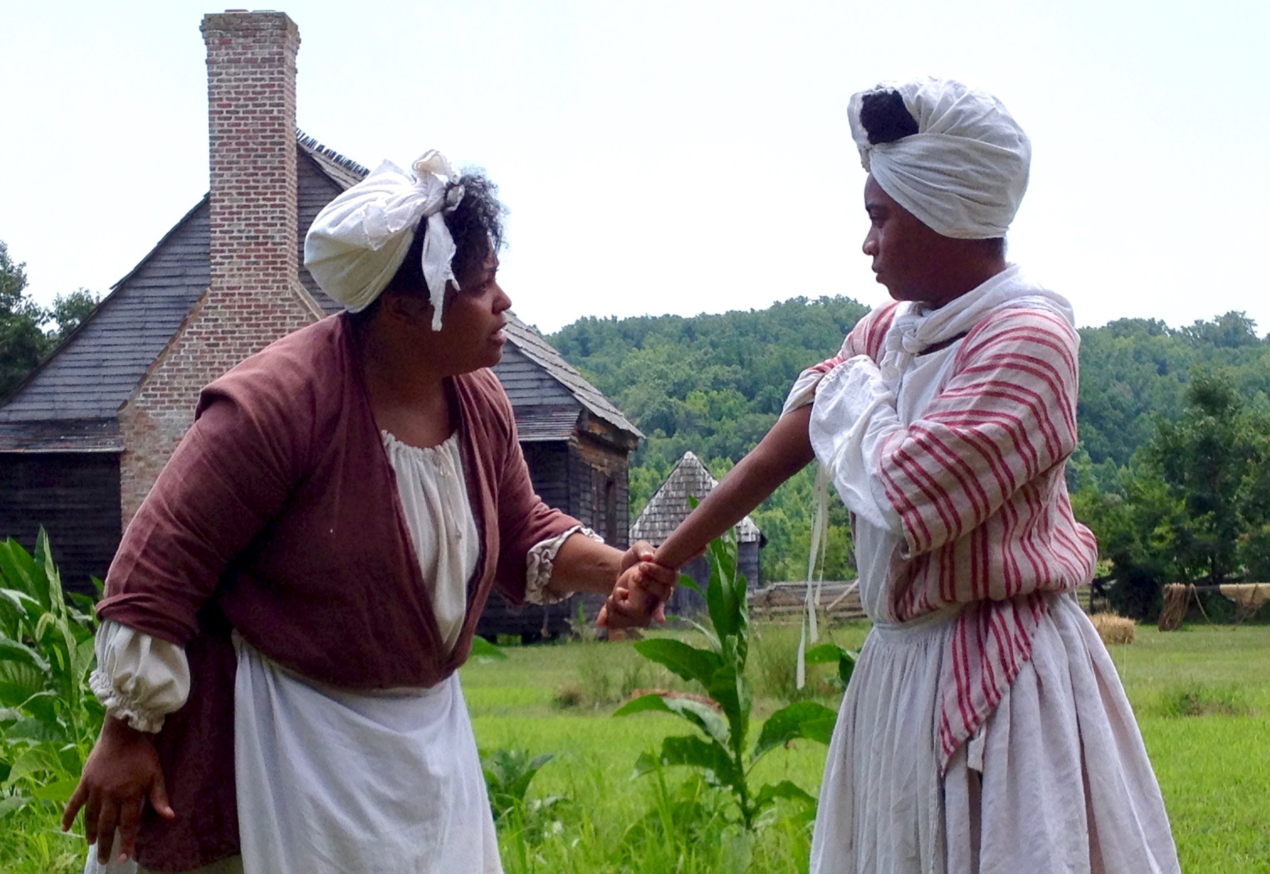 "Shannon Little (on the right) plays the role of ""Cuffy,"" a young enslaved woman in a scripted outdoor play put on by Accokeek Foundation in 2014."