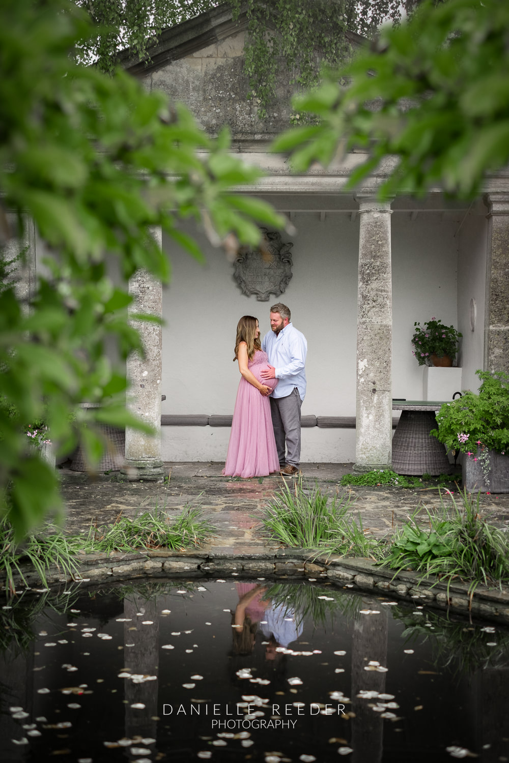 Expectant couple stood in the beautifuol ornamental gardens of Barnsley House