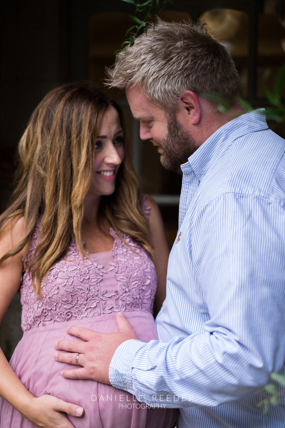 Husband and wife stood gazing at each other during maternity photoshoot