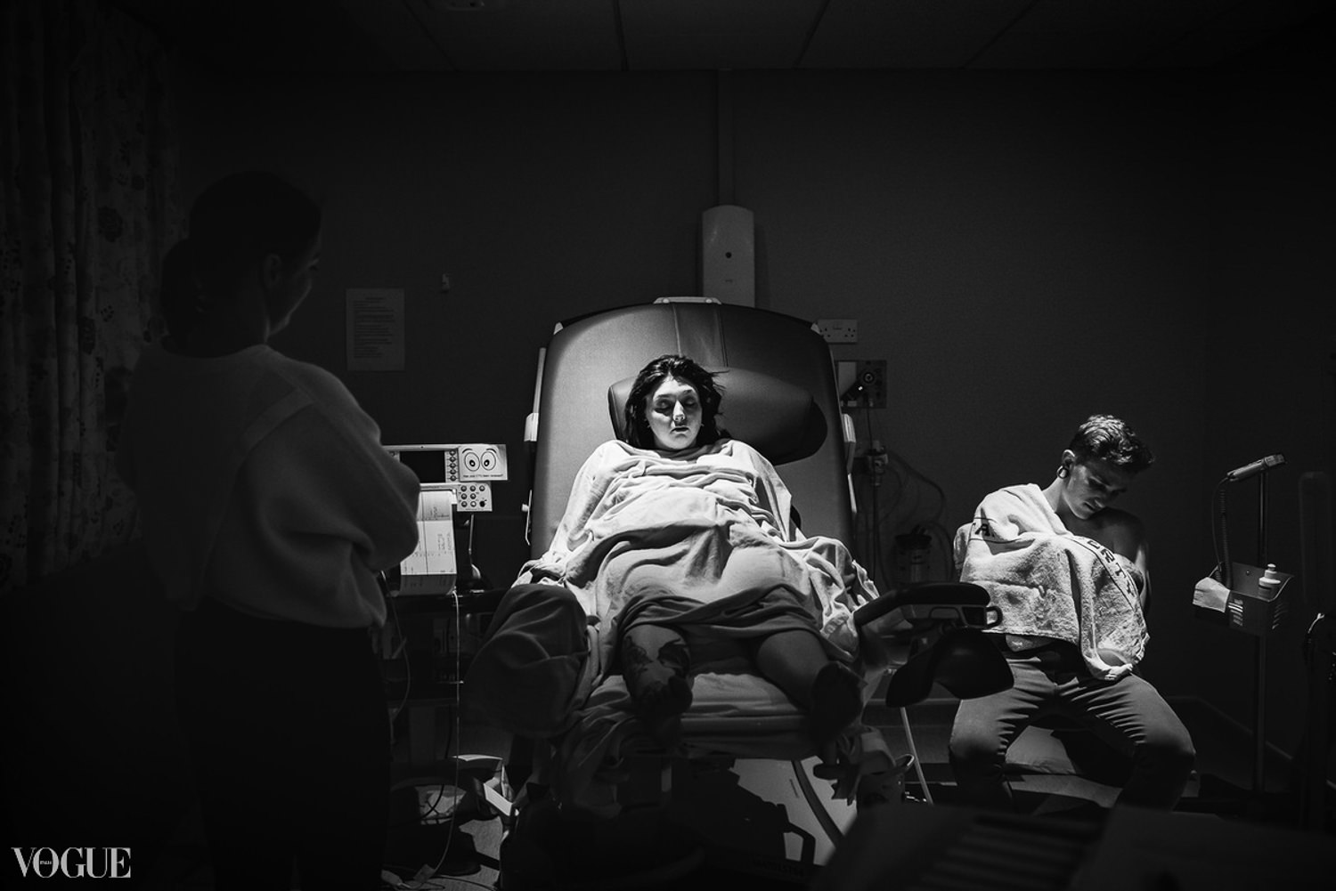Black and white image of postpartum mother laying in hospital sleeping, whilst her mother watches over her and baby is cradled by daddy. As featured on Vogue Italia.
