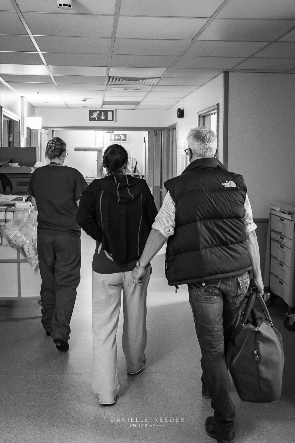 Expectant mother and father following the midwife down the corridor to the delivery suite.