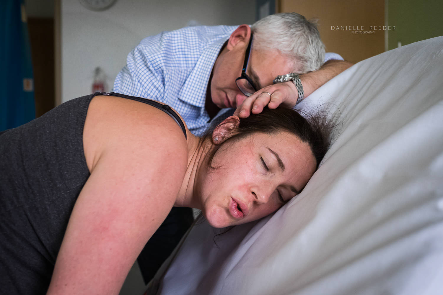 Labouring mother leaning into the back of the hospital bed, breathing out as she works through a contraction.