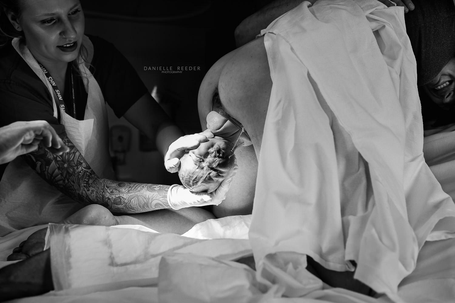 Midwife 'catching' baby as it is born.
