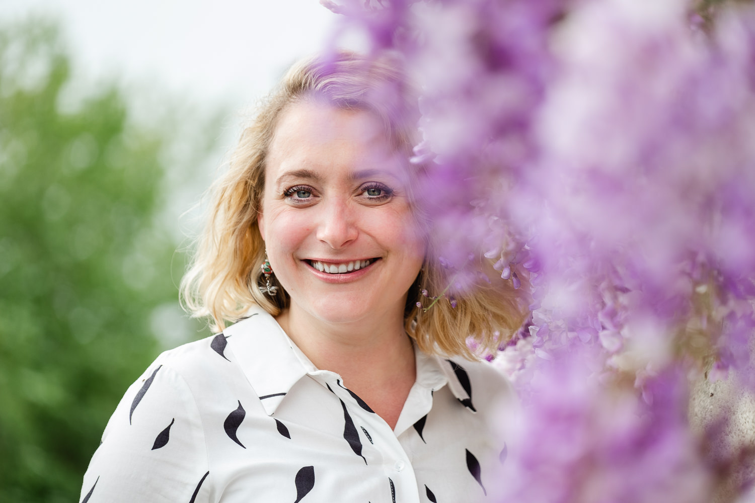 Portrait of Natalia, Clear Desk VA, stood next to vibrant wisteria during her personal branind session in Bristol, Somerset