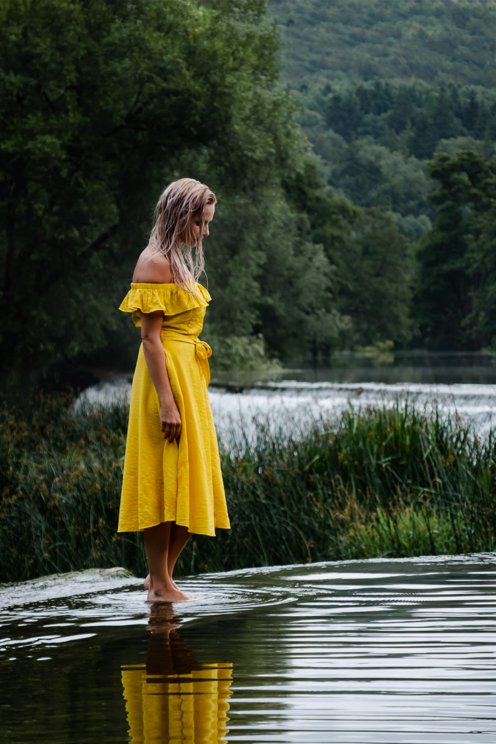 Women stood on the edge of the weir looking down to the rippling water, wearing a mustard yellow dress at Warleigh Weir, Bath.