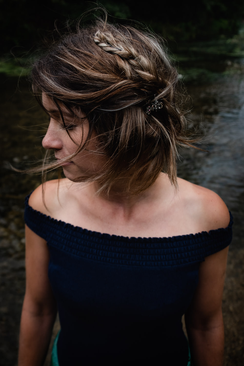 Portrait of a woman, taken from above, stood in shallow water at Warleigh Weir, as the wind blow through her hair.