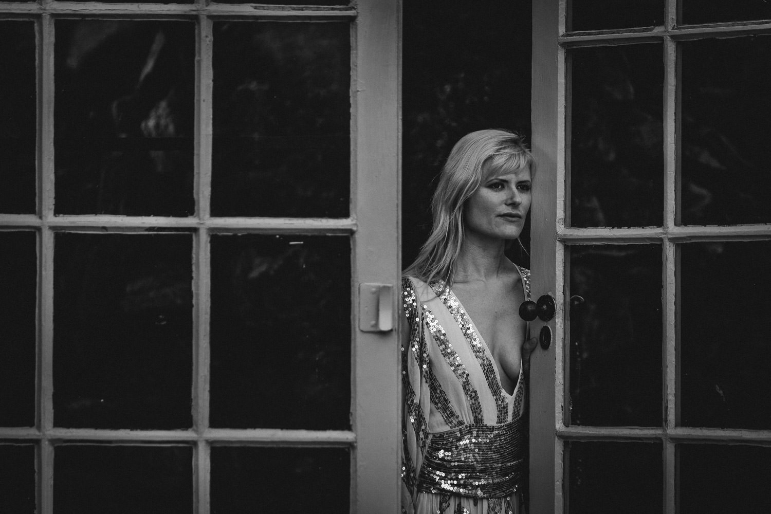Black and white image of a woman, leaning against an open door, as she looks into the distance.