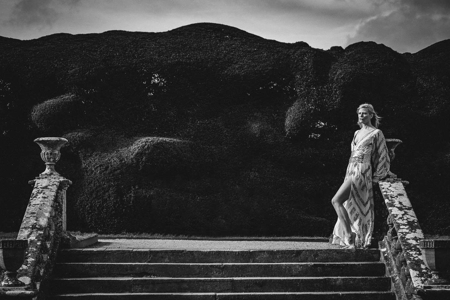 Woman wearing a sequined dress, stood at the top of the steps within the gardens of Montacte House, Somerset.