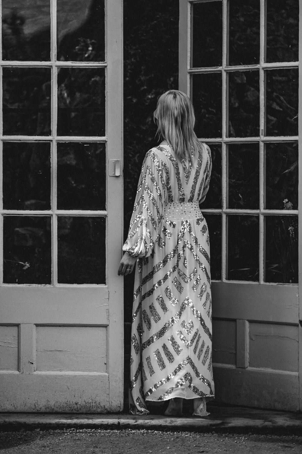 Black and white image of a women walking through doors of an orangery.