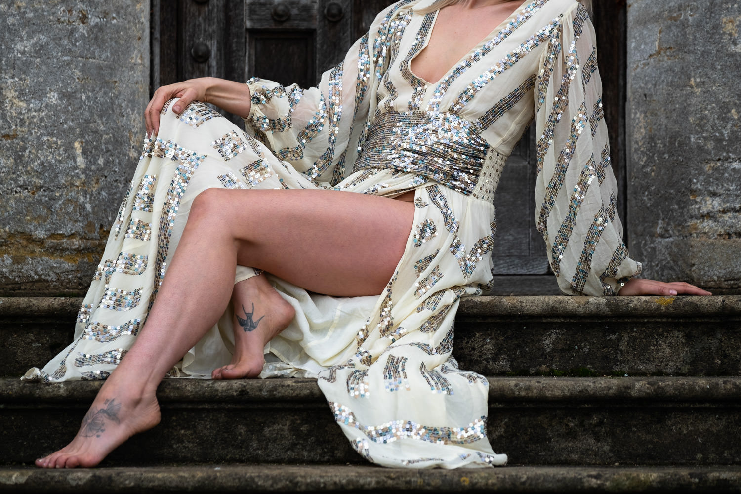 Close up detailed shot of a woman sat on stone steps, wearing a sequined dress.