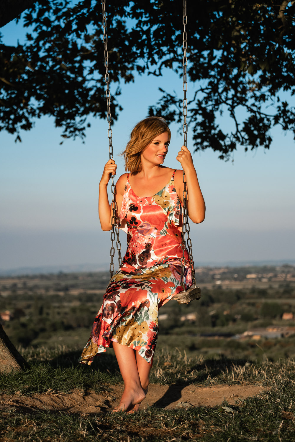 Women sat on the swing at Burrow Hill, Kingsbury Epicopi, wearing a satin floral dress as the winds gently blows her hair back.